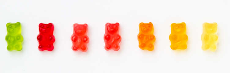 Colorful jelly candy gummy bears on white background. Green, red, orange and yellow colors. Panorama view