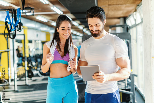 Leinwand Poster Bearded smiling personal trainer showing woman results of training on tablet