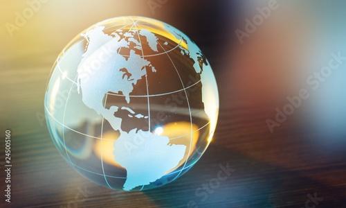 Fototapeta Glass globe ball in light rays on background obraz