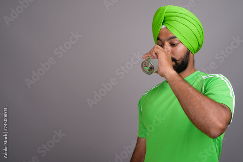 Valokuva Young handsome Indian Sikh man wearing turban and green shirt