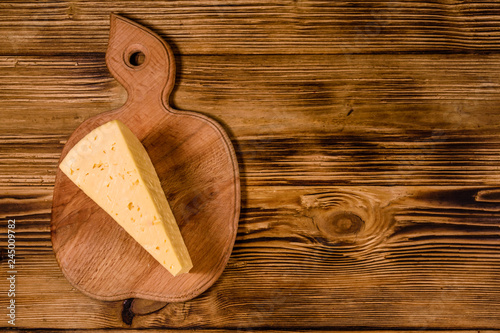 Cutting board with piece of cheese on wooden table. Top view