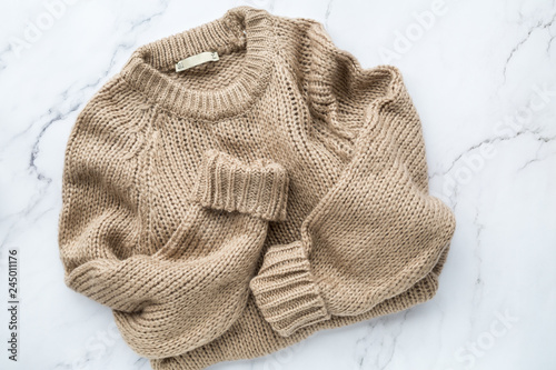 Female beige knitted sweater on white marble background top view flat lay Wallpaper Mural