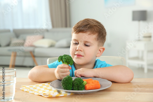 Adorable little boy eating vegetables at table in room