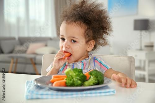 Cute African-American girl eating vegetables at table in living room