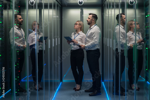 Wide shot of workers with digital tablet in hand in a data center walking between rows of server racks