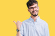 Leinwandbild Motiv Young handsome man wearing glasses over isolated background smiling with happy face looking and pointing to the side with thumb up.