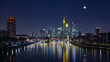 End of lunar eclipse of over the skyline of Frankfurt, Germany, with reflections on the river Main.