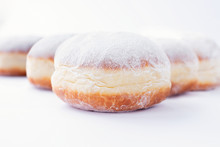 Freshly Made Doughnuts Filled With Jam And Covered In Powdered Sugar On A White Background