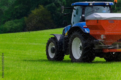 Valokuva  Tractor spreading fertilizer on crops in farm field