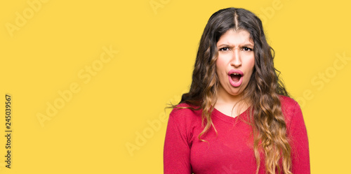 Photo  Young beautiful woman wearing red sweater In shock face, looking skeptical and s