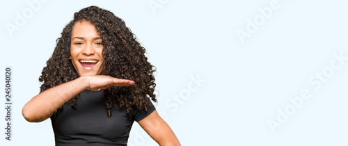 Valokuva  Young beautiful woman with curly hair gesturing with hands showing big and large size sign, measure symbol