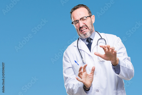 Fotografie, Tablou  Middle age senior hoary doctor man wearing medical uniform isolated background disgusted expression, displeased and fearful doing disgust face because aversion reaction