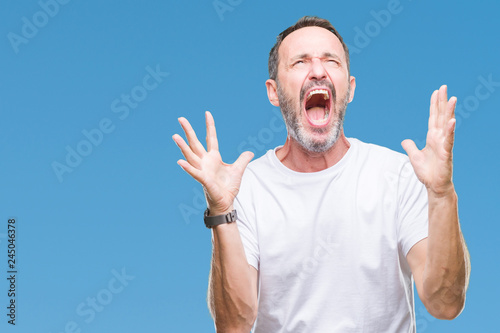 Fotografie, Tablou  Middle age hoary senior man wearing white t-shirt over isolated background crazy and mad shouting and yelling with aggressive expression and arms raised