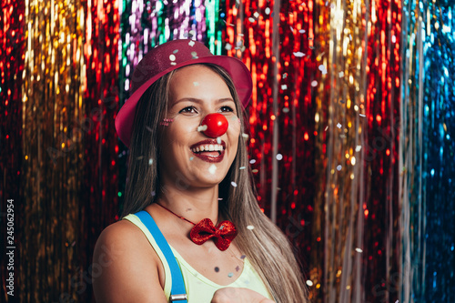 Fotografija  A female clown with colorful clothes and makeup on colorful background