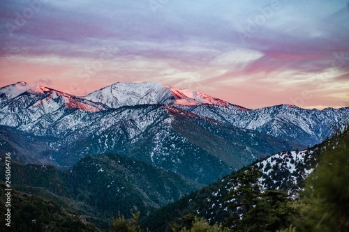 Snowy mountain sunset with pink and purple alpenglow and clouds Wallpaper Mural