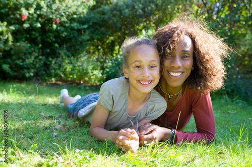 Obraz na plátně  Portrait of smiling mother with daughter laying on grass in garden