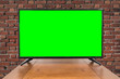 canvas print picture - Modern television on table with brick wall and chroma key green screen.