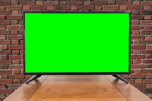 Modern Television On Table With Brick Wall And Chroma Key Green Screen.