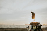 Man standing on a car top at the beach in California, USA