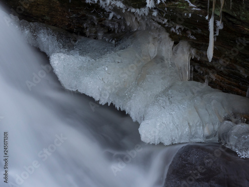 Deurstickers Dam smooth motion of wild water in a river in winter with snow and ice on rocks and stones in the beautiful nature of a forest
