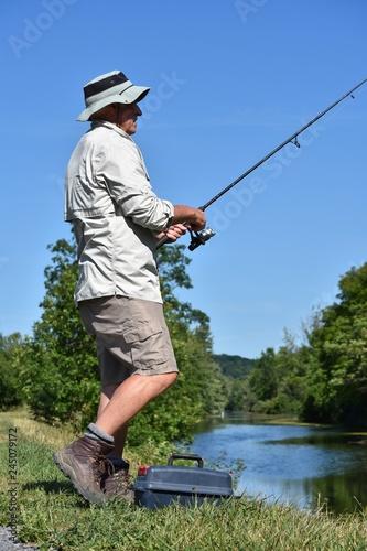 Fotobehang Vissen Older Senior Male Fisherman Standing With Rod And Reel Fishing