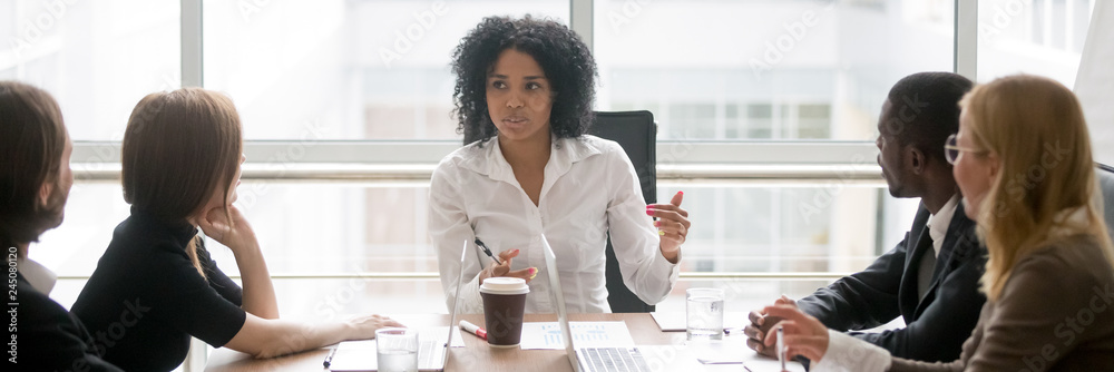 Fototapeta Horizontal photo people sitting at boardroom african business woman talking with staff at formal meeting briefing, diverse client partners listens boss ceo team leader banner for website header design