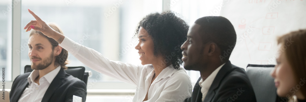 Fototapeta Diverse people sitting at boardroom, african woman raise hand ask question during seminar conference, corporate education or volunteer voting concept. Horizontal photo banner for website header design