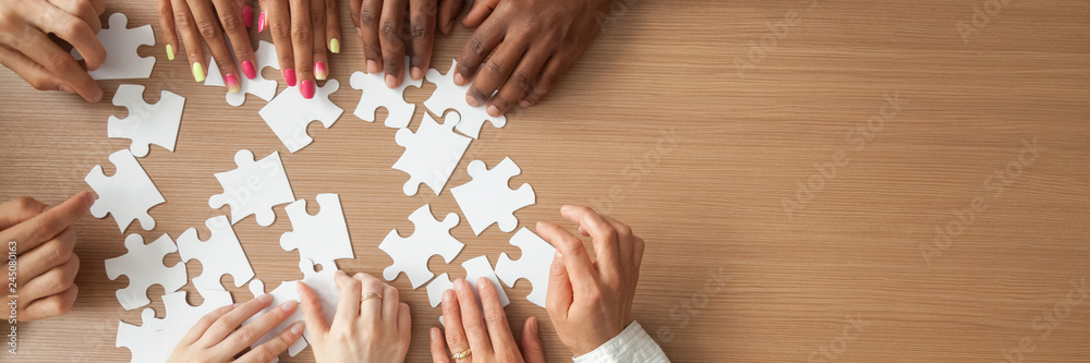 Fototapeta Above top panorama copyspace for text diverse hands people assemble jigsaw puzzle put pieces together search common decision. Support teamwork concept horizontal photo banner for website header design