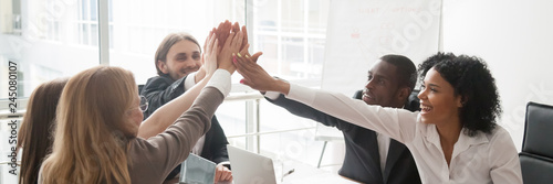 Fotografía  Multi-ethnic business people sitting at desk boardroom celebrating success giving high five feels happy excited, team spirit unity concept