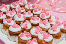 Brown Cupcakes With White Cream And Pink Flowers. Round Little Cookies On A Plate. Cupcakes In White Paper Form. Pastry For Tea. Sponge Cakes.