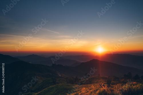 Obraz na plátně  Dramatic sunset and sunrise with sun flare over mountain valley morning twilight evening sky