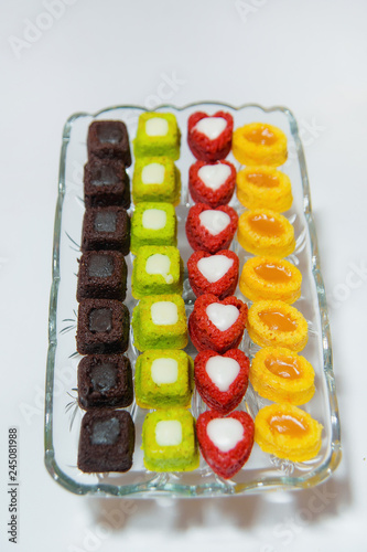 Fotografie, Obraz  Multicolored mini-cakes in a square glass plate