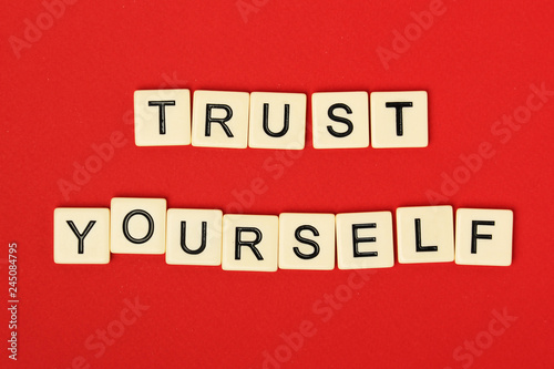 Foto  Inspirational sentence Trust yourself formed with game tiles