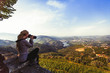Woman photographs river, vineyards are on a hills of Douro Valley - Portugal.