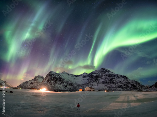 Poster Aurore polaire Fantastic Aurora borealis over snowy mountain with man standing