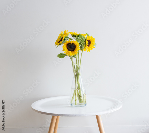 In de dag Zonnebloem Sunflowers in glass vase on small white round table against neutral wall background