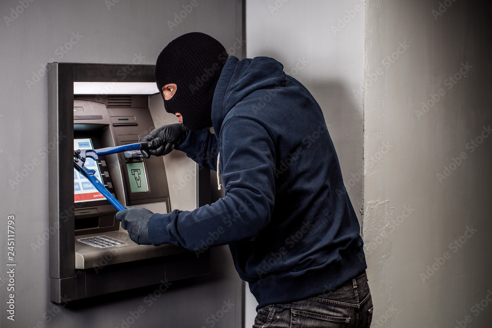 Fototapeta Thief with bolt cutter hacks an ATM. Law and crime concept