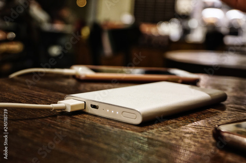 Fotografie, Obraz  Powerbank charging smartphone close up view on wooden background
