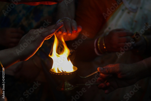 hands taking warmth of Divine diya holy flame of hindu god worship puja for bles Wallpaper Mural