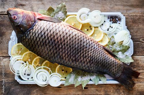 Fototapeta Raw carp with lemon, onion and spices on a metal tray obraz