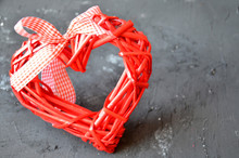 A Red Heart Made Of Wood Texture. A Celebration Of Love. Valentine's Day. Wicker Red Heart With Bow And Ribbon On Black Background