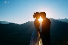Happy Wedding Couple Staying Over The Beautiful Landscape With Mountains During Sunset