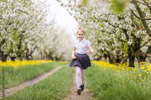 Little blonde girl running in blooming apple and cherry garden. Warm springtime and mothers and woman day