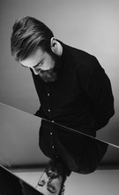 Black And White Photo Of A Man With A Beard And Stylish Hairdo Dressed In The Black Shirt Standing Over The Mirror With Reflection Of His Face