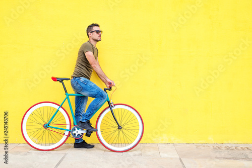 Fotografija  Side view of a young hipster man with a fixed bike wearing casual clothes while
