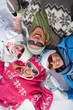 Overhead view of family on winter vacation laying in snow smiling at camera