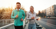 Young Fitness Couple Running In Urban Area