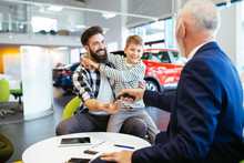 Father And Son Talking With A Salesman About Buying A New Car At The Car Showroom.