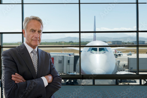 Fotografie, Obraz  Serious mature businessman on trip standing in airport terminal looking at camer