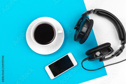 Fototapeta Headphones and coffee cup on blue background, top view obraz na płótnie